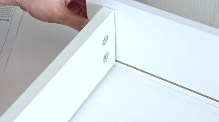 монтаж : Close up view of a person assembling new white drawer using a screwdriver Стоковые видеозаписи