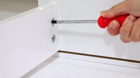 do it yourself : Close up view of a person assembling new white drawer using a screwdriver Stock Footage