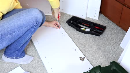 do it yourself : Woman assembling white furniture, she tighten a screw with a screwdriver Stock Footage