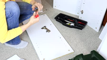 арматура : Woman assembling white furniture, she tighten a screw with a screwdriver Стоковые видеозаписи