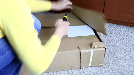 sealed : Woman unboxing a cardboard box with new furniture with construction or office knife - moving to new house and purchasing new furniture