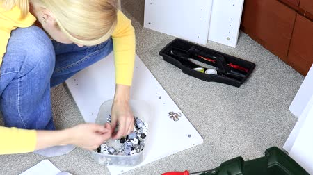 монтаж : Woman assembling white furniture, she tighten a screw with a screwdriver Стоковые видеозаписи