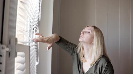 escritórios : Curious young woman spying, peeking through the blinds in her home