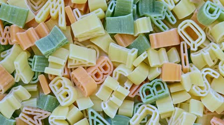 маслянистый : Alphabet kids italian pasta of different colors close up texture rotation background