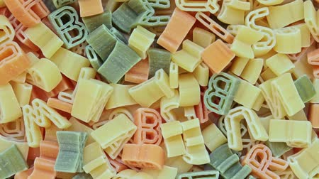 snack : Alphabet kids italian pasta of different colors close up texture rotation background