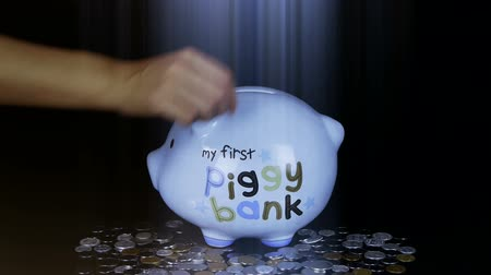 adósság : Piggy bank coin drop in black space,Piggy Bank Savings RMB and rays lights.