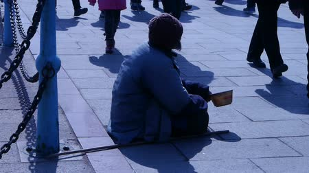 illegal alien : Beggar woman sitting on ground.