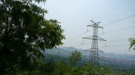 disjuntor : High-voltage wire tower in urban city,wind tree,distant mountain & hill. Vídeos