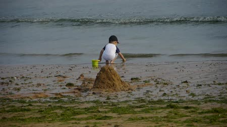 etkinlik : Child play digging sand at the beach.Dune,tide,tidal.