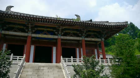 határkő : China ancient temple architecture in forest,blue sky & white clouds between eaves. Stock mozgókép