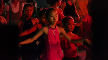 латинский : Dancing Chinese childrens crowd in the square at night.
