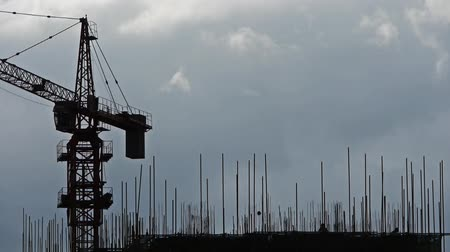 mühendislik : Construction-cranes,clouds cover sky,building high-rise,House silhouette.Construction worker working on roof.