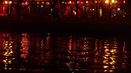 peking : reflection on lake with splendid China ancient architectural lighting at night.pedestrian on shore,BeiJing HouHai.