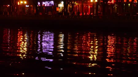 peking : reflection on lake with splendid China ancient architectural lighting at night.pedestrian on shore.BeiJing HouHai.