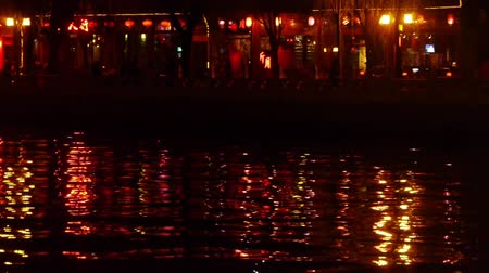 japan : reflection on lake with splendid China ancient architectural lighting at night.pedestrian on shore.BeiJing HouHai.