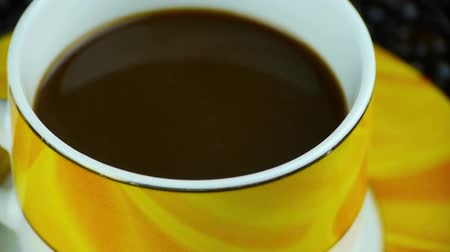 coffe : rotating a cup of coffee & coffee beans background,top view. Stock Footage