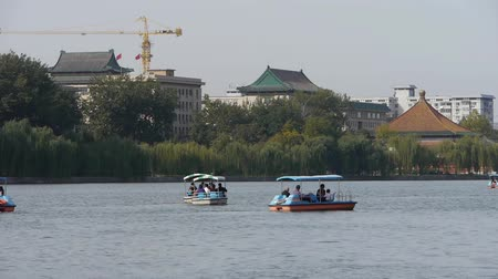 peking : People boating at China Beijing Beihai Park & willow island. Stock mozgókép