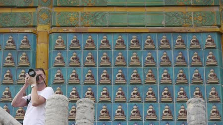 fazilet : tourist photography & ancient east buddha totem wall.  Stok Video