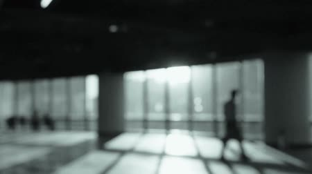 reflexão : blur backgrounds of a person walking in business building inside platform,sunset rays light pass window.