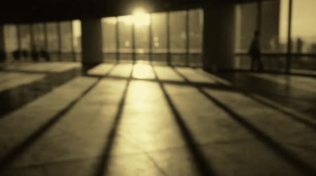 uzun boylu : blur backgrounds of a person walking in business building inside platform,sunset rays light pass window.