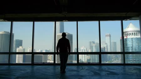 skyscraper : a businessman walking to windows & outlook business building. Stock Footage