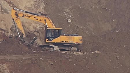 экскаватор : excavator working & dumper truck on construction site. Стоковые видеозаписи