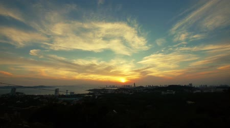 puffy clouds : timelapse sunset clouds,seaside urban skyline & forest. Stock Footage