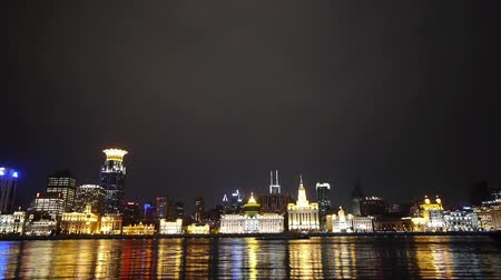 margem do rio : view Shanghai Bund from pudong at night,old europe style building neon lights reflect on huangpu river,water waves.