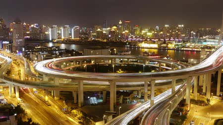 prędkość : Timelapse,driving & cars racing by with streaking lights trail on overpass at night in shanghai,super long exposures for each frame,Brightly lit urban building,busy shipping sailing on huangpu river. Wideo