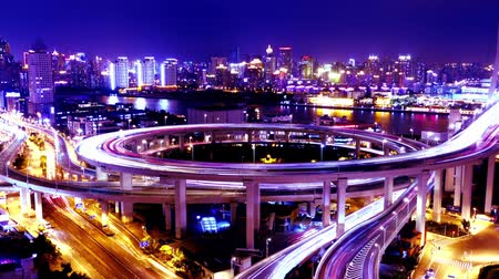 streaking : Timelapse of driving & cars racing with streaking purple lights trail on overpass bridge at night in shanghai with super long exposures for each frame,Brightly lit urban morden building,busy shipping on huangpu river. Stock Footage