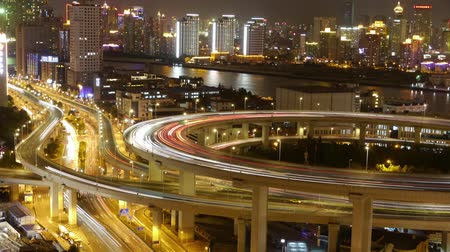 streaking : Timelapse,driving & cars racing by with streaking lights trail on overpass at night in shanghai,super long exposures for each frame,Brightly lit urban building,busy shipping sailing on huangpu river. Stock Footage