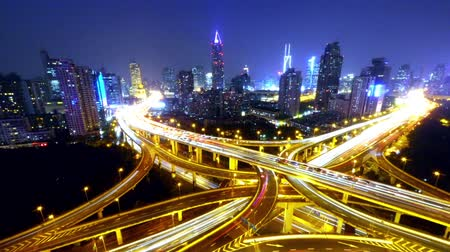 řídit : Timelapse of freeway busy city rush hour heavy traffic jam highway Shanghai at night,Yanan East Road Overpass interchange,the light trails of traffic with super long exposures,Brightly lit urban morden building.