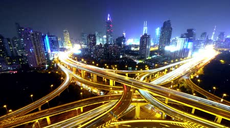 encruzilhada : Timelapse of freeway busy city rush hour heavy traffic jam highway Shanghai at night,Yanan East Road Overpass interchange,the light trails of traffic with super long exposures,Brightly lit urban morden building.