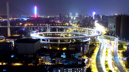streaking : Timelapse of driving & cars racing with streaking lights trail on overpass bridge at night in shanghai with super long exposures for each frame,Brightly lit urban morden building,busy shipping on huangpu river. Stock Footage