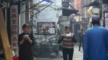 jiangsu : traditional Chinese old town houses & street,Chinese residents life,Women eating noodles in street,some students drawing.