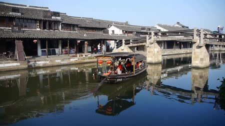 jiangsu : boating through traditional chinese ancient houses reflection on blue water,water town resident life,shanghai,China.