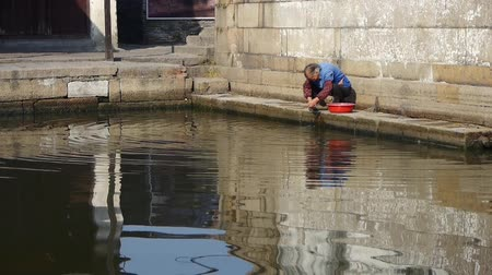 tradicional : chinese old woman wash cloths under bridge,tradition china water town life.