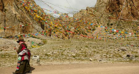 hacı : Tibetans walking the pilgrim at the lake namtso in tibet,Prayer flags in the wind,ancient holy monk meditation in cave,ZhaXi Peninsula,tibet mansarovar  Stok Video