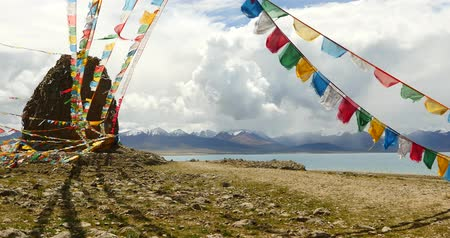 божество : 4k huge clouds mass rolling over lake namtso & Tanggula snow mountain peak,tibet mansarovar,pray flag in wind,Tibets second largest lake,is the third largest saltwater lake in China.Danggula(Tanggula) Mountains in xizang Plateau,roof of the World. Стоковые видеозаписи