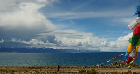 meditação : 4k Tibetans walking the pilgrim at the lake namtso in tibet,Prayer flags in the wind,ancient holy monk meditation in cave,ZhaXi Peninsula,tibet mansarovar,Tibets second largest lake,is the third largest saltwater lake in China.Danggula(Tanggula) Mou