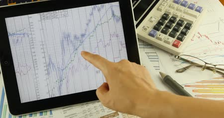 waarden : Zakenman werken op de tablet met diagrammen, vinger aanraken finance markt cirkeldiagrammen Graph op het computerscherm, business analyse rapport document & rekenmachine op tafel.
