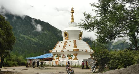 tanítvány : tibet people walking around buddhist white stupa in village,cloud cover mountain.
