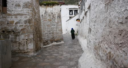 rústico : tibet woman walking on the lhasa drepung,famous tibetan temple,ancient buddhist building. Stock Footage
