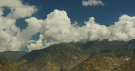 tramp :  white puffy clouds mass rolling over Tibet mountaintop  valley,roof of the World.