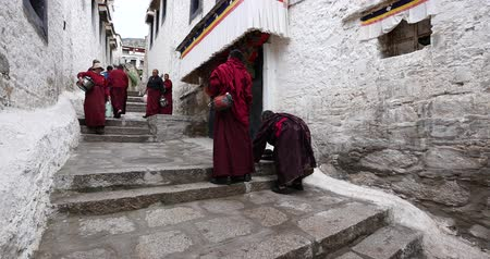 rústico : tibet monks walking on the lhasa drepung,famous tibetan temple,ancient buddhist building.