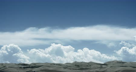 cena não urbana :  timelapse great white puffy cloud mass rolling over desert sand,dunes plateau landform. Vídeos