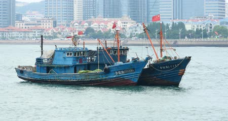 deep seaport : boats floating in the sea against urban building background.