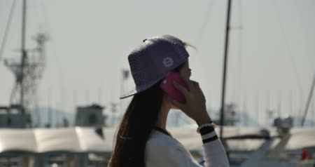 portátil : A girl using a smartphone at seaside,yacht  sailing in the harbour. Stock Footage