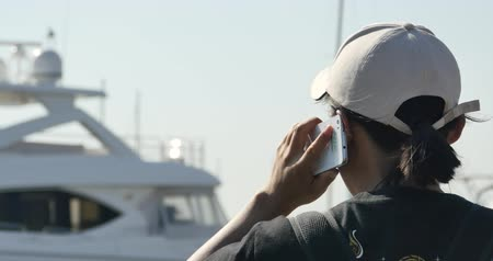 portátil : A human using a smartphone at seaside,yacht  sailing in the harbour. Stock Footage
