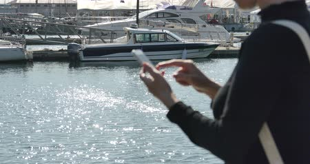 gelişme : A girl using a smartphone at seaside,yacht  sailing in the harbour,Sparkling water surface.